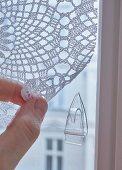 Transparenter Klebehaken an Fenster für gehäkeltem Vorhang