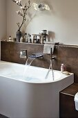 A designer bathtub with a fountain tap and shower head attached to a tiled wall panel