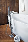 A freestanding white bath with an elegant standing tap