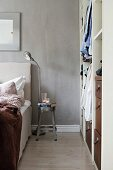 Metal stool used as bedside table against grey wall next to open-fronted cupboard