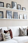 Scatter cushions in earthy tones on white sofa below pictures on narrow shelves
