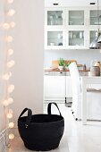 Fairy lights and black rubber basket in front of open-plan kitchen with dining area