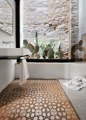 Traditional tiled floor and cacti against stone wall in bathroom