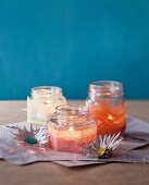 Hand-made candles in screw-top jars decorated with lace trim