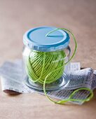 Green yarn in screw-top jar with hole in lid