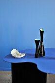 Blauer Designertisch vor gleichfarbigem Raumteiler