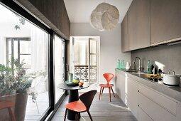 Küchenzeile und kleiner, runder Tisch mit Designerstühlen vor Glasschiebetür