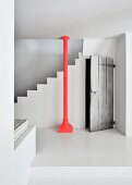 Red steel column in front of white concrete staircase next to rustic board door