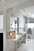 Concrete washstand with wall-mounted taps in front of shower area