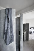 Grey towel hung over concrete cylindrical shower and view into bedroom