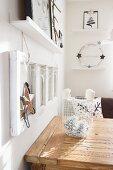 Weisser Metallkorb mit Zapfen und Kerzen auf Holztisch, an Wand Weihnachtsdekoration mit Bilderrahmen