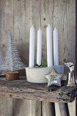 Kerzendekoration, stilisiertes Weihnachtsbäumchen, Silberstern und Silberglocke auf Holzunterlage