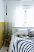 Black and white striped blanket on bed below window