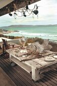 Flotsam and wooden figurines on weathered coffee table on castors on wooden deck with sea view