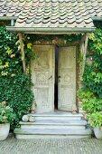 Vintage Eingang mit traditionellen geschnitzten Holztüren, Vordach und begrünter Fassade