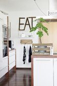 Small green tree in rustic wooden crate with motto on kitchen counter and decorative lettering on wall