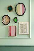 Assorted photo frames containing Biedermeier fabrics on a paste-green wall wth moulding