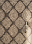 Ornamental non-woven wallpaper with a lace pattern in shades of beige