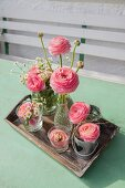 Ranunculus in various vases on wooden tray