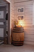 Arrangement of candles on top of old wooden barrel in wooden cabin