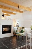 Comfortable armchair next to fireplace in country house with wood-beamed ceiling and black floor tiles