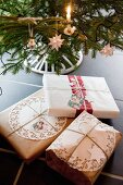 Gifts wrapped in vintage-style packaging below Christmas tree