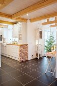 Brick-built counter in country-house kitchen adjoining open-plan living area with Christmas tree in background