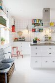 Retro scales, colourful tins and island counter in white fitted kitchen