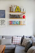 Grey couch with various scatter cushions below books and decorative letters on String shelves