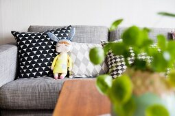 Stofffigur auf grauer Couch mit verschiedenen Kissen
