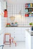 weiße Einbauküche mit Retro Küchenwaage und bunten Blechdosen auf String-Regal