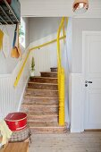 Rustic wooden staircase with yellow handrail and newel post in renovated period building