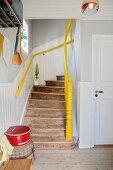 Rustikaler Holztreppenaufgang mit gelbem Handlauf und Treppenpfosten in renoviertem Altbau