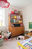Various small cases, toys and soft toys on retro dresser in girl's bedroom