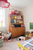 Retro Schrank in Mädchenzimmer mit verschiedenen Köfferchen, Spielzeug und Plüschtieren