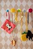 Various children's bags hung from colourful pegs on diamond-patterned wallpaper