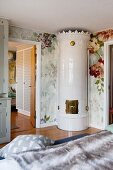 Elegant hand-crafted tiled stove in corner of bedroom with floral wallpaper
