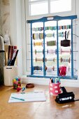 Craft materials and wooden frame holding reels of string and ribbon on windowsill above desk