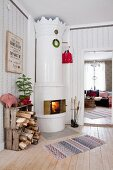 Fire in white-tiled Swedish stove with ornate top in festive Scandinavian interior