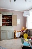 Vintage wooden bed, fairy lights, vintage cupboard and contemporary toys in child's bedroom