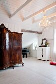 Artistically carved, antique wardrobe and chandelier in vintage-style, whit attic room