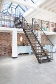 Steel stairs leading to two gallery levels in loft apartment with concrete floor and rustic brick wall