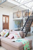 Antique front door, steel stairs leading to gallery and comfortable sofa in loft apartment