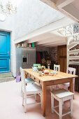 Dining table, vintage chairs and blue panelled door in loft apartment