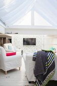 White loose-covered furniture and wall-mounted TV on floral wallpaper in bright TV room
