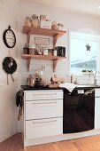 Kitchen base units below storage jars and Christmas decorations on wall-mounted shelves