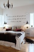 Animal-skin rug and scatter cushions on double bed below motto on wall of bedroom