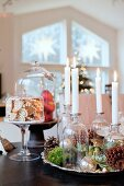 Hand-made Advent wreath with four lit candles in apothecary bottles, gingerbread and apples under glass cover