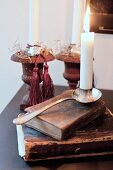 Lit candle in silver candlestick on old books