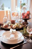 Festive place setting and Christmas decorations on table